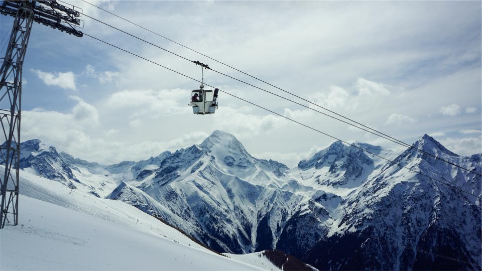 gondola lift snowboarding skiing snow winter mountains peaks sky clouds hill