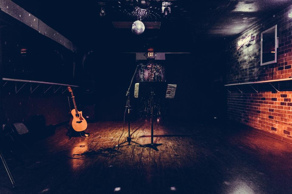 musician guitar singer songwriter bar dive bar microphone disco ball brick nightlife club