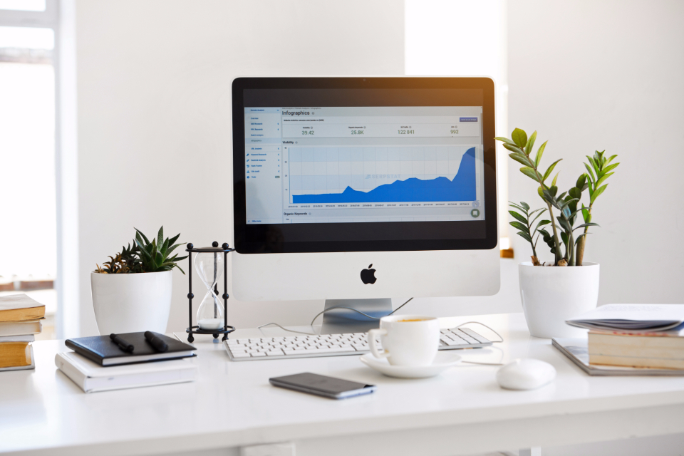 seo computer macbook marketing digital charts graphs analytics business technology office desk work mouse coffee notebook notepad plant decor finance books mobile screen monitor