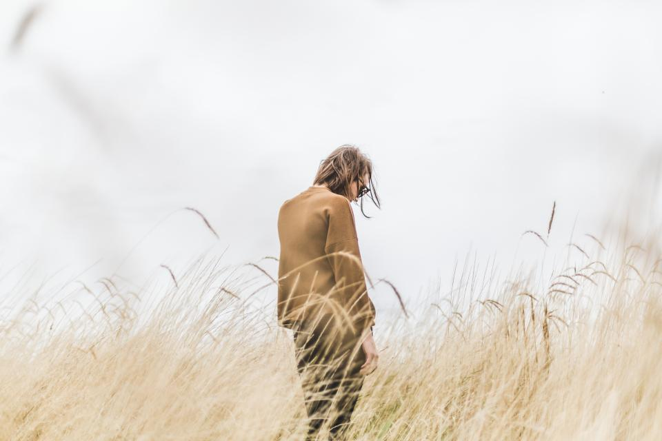 girl alone thinking mountain nature grass view brown model clouds people