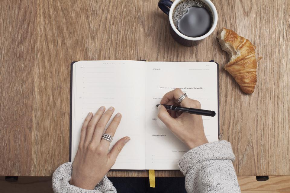 journal notepad notebook pen writing hands office desk business working coffee cup mug croissant food meeting