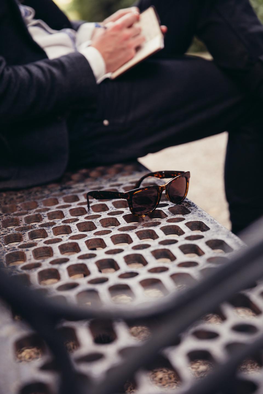 people man sitting alone steel metal bench outdoor sunglasses eyewear
