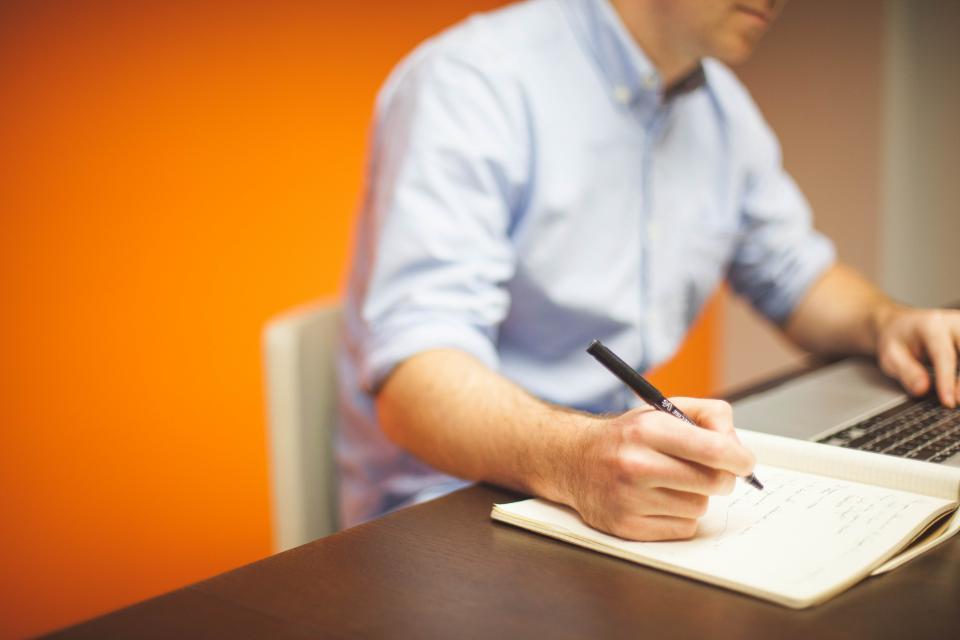 business working office desk laptop macbook computer technology writing notebook pen blogging