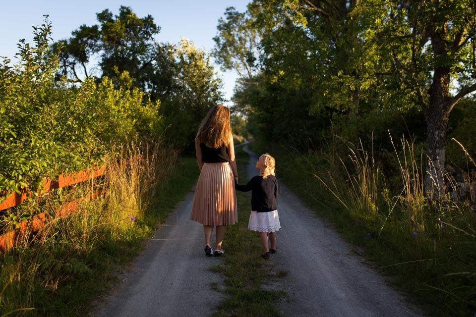 people kid child girl mother woman walking path road green grass plant trees nature sunny day