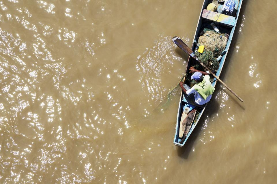 people man boat water sea dirty crops paddle poverty