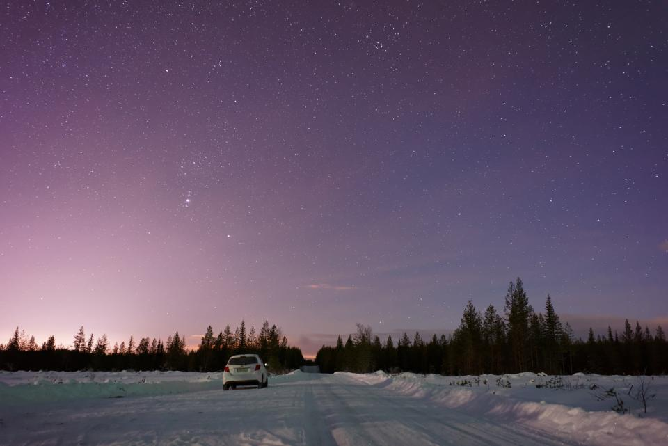 Car driving in snow stars sky