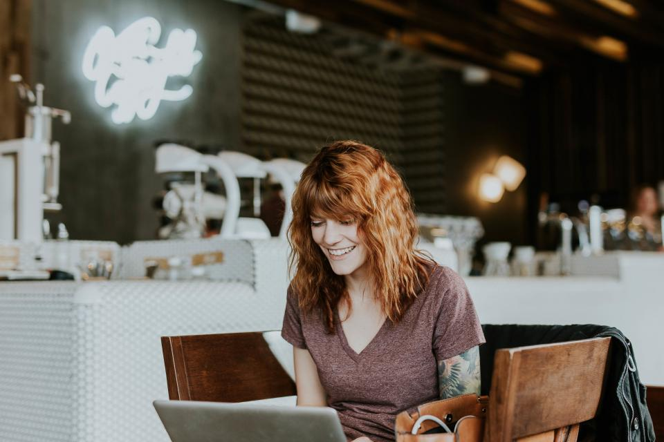 laptop electronic gadget communication research internet browser business woman people smile happy restaurant table chair inside blur signage